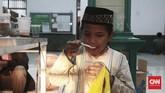 Seorang anak yang sedang menikmati minuman berbuka puasa di salah satu musola kampung Jawa, Bali. Musola Nurul Iman selalu diramaikan orang yang sengaja menunggu waktu berbuka. (CNN Indonesia/Andry Novelino)