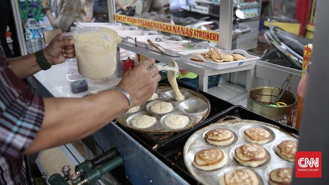 Pedagang kue kamir di pasar takjil Kebon Kacang menjajakan jualannya yang masih hangat karena memasaknya di tempat.(CNN Indonesia/ Hesti Rika)