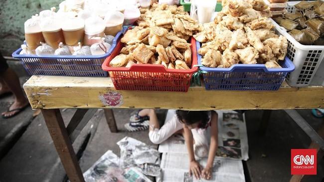 Seorang anak membaca koran sambil menemani orang tuanya menjajakan makanan khas buka puasa di pasar takjil Kebon Kacang.(CNN Indonesia/ Hesti Rika)
