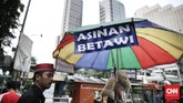 Penjual asinan Betawi di pasar takjil Kebon Kacang tengah menunggu pembeli dengan latar belakang gedung perkantoran di daerah tersebut.(CNN Indonesia/ Hesti Rika)