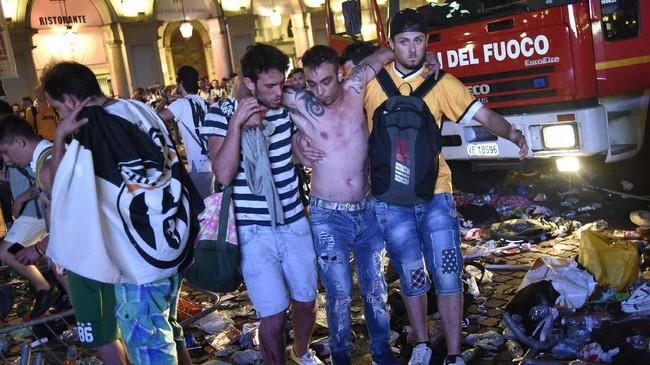 Dalam kericuhan tersebut, berbagai benda melayang ke udara, seperti sepatu, botol bir, tas, dan berbagai benda lainnya. Orang-orang pun banyak yang pincang setelah terinjak-injak. (REUTERS/Giorgio Perottino)