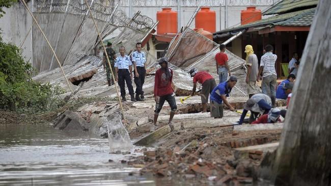 <p>Petugas lapas bersiaga di sekitar para pekerja yang membuat pondasi pagar darurat di lokasi bekas bangunan dinding Lapas Klas II A Jambi yang ambruk akibat banjir di Jambi, Kamis (15/6). (ANTARA FOTO/Wahdi Septiawan)</p>