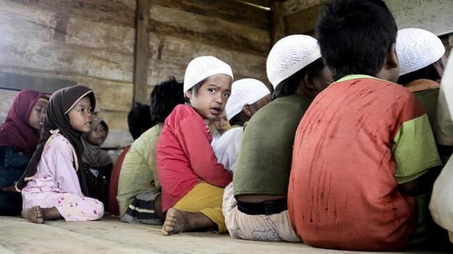 Suasana mengaji anak-anak Orang Rimba di sebuah rumah kayu. Anak-anak ini sekarang punya aktivitas lain selain menemani orang tua mereka berburu di hutan. (AFP PHOTO / GOH CHAI HIN)