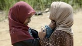 Mereka juga mendapat bantuan pakaian sehingga tak lagi harus mengenakan cawat seadanya. Tampak dua gadis Orang Rimba tengah mengenakan jilbab dan bersiap-siap untuk belajar mengaji.(AFP PHOTO / GOH CHAI HIN)