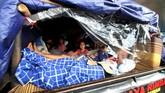 Pemudik menaiki mobil pikap yang tertutup terpal saat arus balik mudik Lebaran 2017 di Gerbang Tol Cikarang Utama, Jawa Barat, Jumat (30/6). Untuk menghindari kemacetan, Polri dan Jasa Marga membuka pintu pembayaran atau gate menjadi 31 pintu. (ANTARA FOTO/Rivan Awal Lingga/foc/17)
