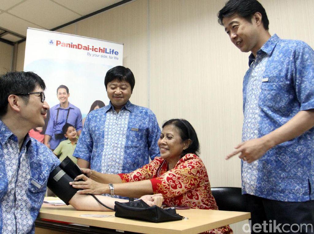 Wakil Presiden Direktur PT Panin Dai-ichi Life Simon Imanto (kiri), disaksikan Wakil Presiden Direktur Masayuki Tanaka (kedua kiri) dan Direktur Koichi Nishiyama (kanan) ikut diperiksa tekanan darahnya di kantor Panin Dai-ichi Life di Jakarta, Jumat (7/7).