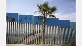 <p>Amerika Serikat dan Meksiko dipisahkan oleh perbatasan sepanjang 3.200 kilometerdari Teluk Meksiko di timur hingga ke Samudera Pasifik di Barat. Di antara ribuan kilometer itu, banyak bagian perbatasan yang berubah jadi kanvas mural. (AFP PHOTO / GUILLERMO ARIAS)</p>