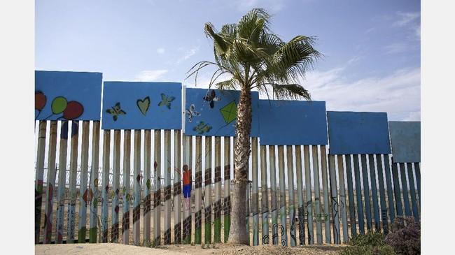 Amerika Serikat dan Meksiko dipisahkan oleh perbatasan sepanjang 3.200 kilometerdari Teluk Meksiko di timur hingga ke Samudera Pasifik di Barat. Di antara ribuan kilometer itu, banyak bagian perbatasan yang berubah jadi kanvas mural. (AFP PHOTO / GUILLERMO ARIAS)