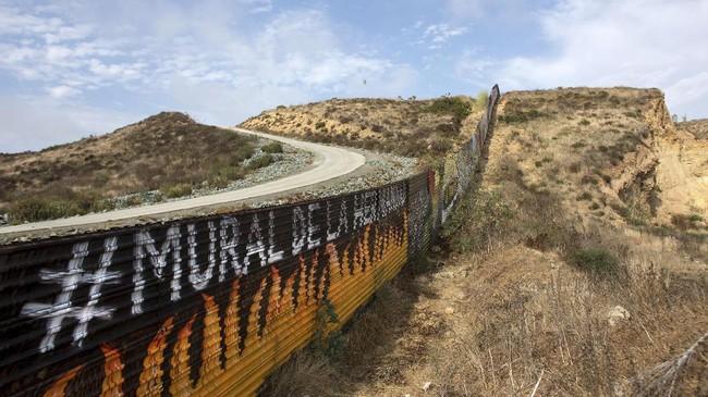 Beragam kata bernada perdamaian ditorehkan di tembok itu, seperti 'unity', 'equality', 'art', dan 'freedom', baik dalam bahasa Inggris maupun Spanyol. (AFP PHOTO / GUILLERMO ARIAS)