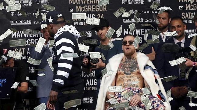 <p>McGregor yang sempat tak mengacuhkan aksi Mayweather Jr. lantas berteriak, uang uang dihamburkan calon lawannya itu palsu. Padahal, itu merupakan uang asli. (Noah K. Murray-USA TODAY Sports TPX IMAGES OF THE DAY)</p>