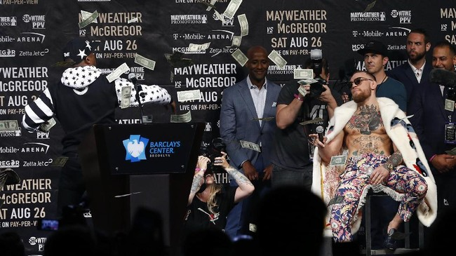 <p>Floyd Mayweather Jr. langsung melempar lembaran uang kertas pecahan US$ 1 ke depan Conor McGregor. (Noah K. Murray-USA TODAY Sports)</p>