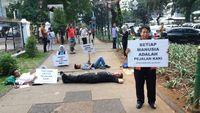 Dalam aksi tersebut, para anggota Koalisi Pejalan Kaki menghalau pemotor yang ingin melintas di trotoar dengan berbaring di jalanan. (Foto: Koalisi Pejalan Kaki)