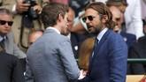 Aktor Eddie Redmayne (kiri) dan Bradley Cooper terlihat berbincang dengan serius sebelum pertandingan final. (REUTERS/Andrew Couldridge)