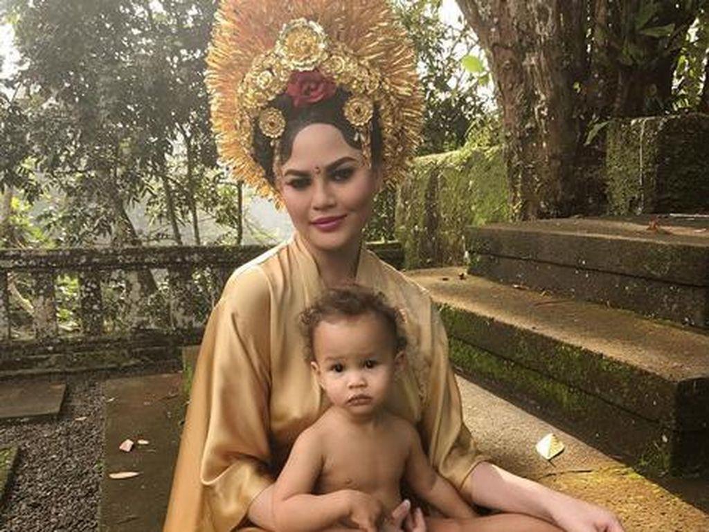 Chrissy tampak cantik menawan kala menggendong Luna dengan busana adat Bali. (Dok. Instagram/chrissyteigen)
