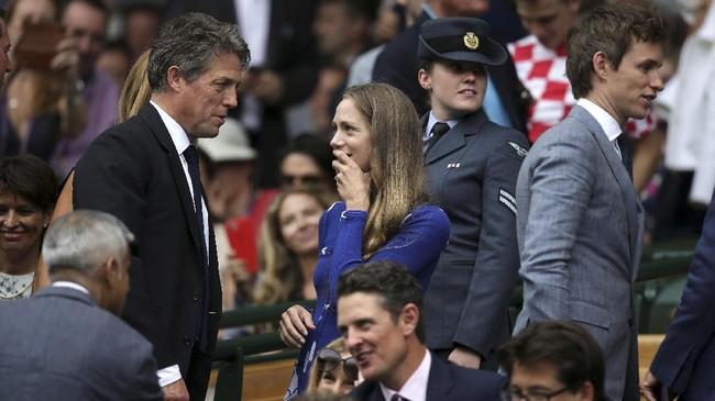 <p>Aktor kawakan Inggris, Hugh Grant (kiri), terlihat berbicara dengan istri Eddie Redmayne, Hannah Redmayne, sebelum final Roger Federer melawan Marin Cilic. (REUTERS/Daniel Leal-Olivas/Pool)</p>