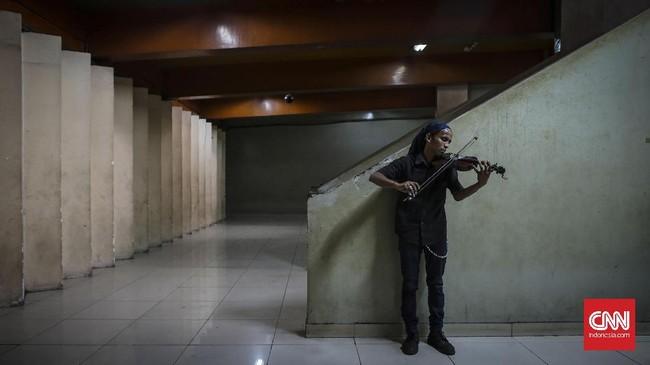 Danang, pengamen biola yang sering mangkal di kawasan Terminal Blok M pun ikut merasakan sepinya pengunjung, ini juga berpengaruh dengan pendapatannya. (CNNIndonesia/Safir Makki)