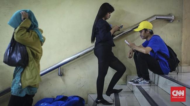 Pengunjung duduk di anak tangga penghubung Terminal dan Mal Blok M. Meskipun mal ini sudah berbenah dan mempercantik interior, kesepian menjadi ancaman pedagang. (CNNIndonesia/Safir Makki)
