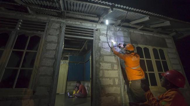 Petugas PLN memeriksa aliran listrik melalui alat meter listrik di Desa Lifuleo, Kupang, Nusa Tenggara Timur, Kamis (20/7) malam. PT PLN (Persero) menargetkan 500 desa di wilayah NTT dapat teraliri listrik dari jaringannya hingga akhir tahun 2017 guna mewujudkan 100 persen desa berlistrik di NTT. (ANTARA FOTO/Widodo S Jusuf)