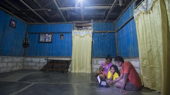 Ribka Tosi (kiri) mendampingi anaknya belajar mengunakan komputer jinjing di rumahnya di Desa Lifuleo, Kupang, NTT, Kamis (20/7). Penyediaan listrik andal dan berkualitas masih menjadi persoalan di Indonesia. (ANTARA FOTO/Widodo S Jusuf)