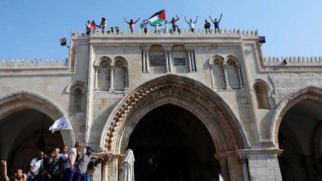 Warga Palestina berkumpul di Yerusalem timur guna merayakan kembalinya status quo ke kawasan tersebut. Mereka turun ke jalan dan mengibarkan bendare serta bersorak-sorai merayakan kemenangan. (REUTERS/Muammar Awad)