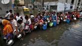 Bnajir membuat warga India banyak yang kekurangan makanan dan air bersih. Terlihat warga mengantri air bersih di tanki kota di Ahmedabad. (REUTERS/Amit Dave)