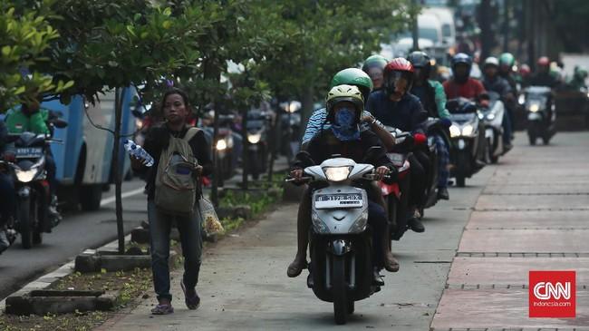 Barisan motor otor beriringan melintasi trotoar khusus pejalan kaki saat macet di kawasan Casablanca, Jakarta. Perilaku tak disiplin pengendara motor yang banyak dikeluhkan pejalan kakin ini akan ditindak tegas pada bulan tertib trotoar di kawasan Jakarta. (CNNIndonesia/Safir Makki)
