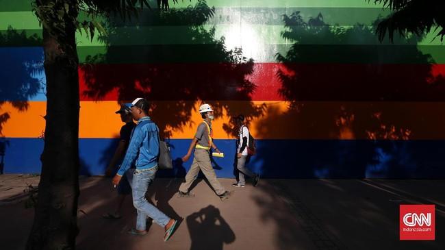 Pejalan kaki dengan nyaman melewati trotoar yang lebar di kawasan Sudirman, Jakarta. Sanksi bagi pelanggar fungsi perlengkapan jalan, salah satunya trotoar sebagai sarana pejalan kaki, adalah ancaman penjara maksimum satu tahun atau denda paling besar Rp24 juta. (CNNIndonesia/Safir Makki)