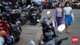 Pejalan kaki terpaksa berjalan di ruas jalan karena trotoar pejalan kaki dialihfungsikan sebagai lahan parkir motor. Kekurangan sarana lahan parkir motor gedung perkantoran menyebabkan parkir-parkir liar di trotoar menjamur. (CNNIndonesia/Safir Makki)