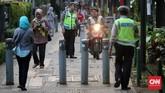 Polisi menindak pengendara motor yang masuk ke trotoar pejalan kaki di kawasan Kebon Sirih, Jakarta. Aturan tentang trotoar merupakan hak eksklusif pejalan kaki ada pada sesuai Pasal 34 ayat (4) Peraturan Pemerintah 34/2006 tentang Jalan dan Undang-Undang tentang Lalu Lintas dan Angkutan Jalan (UU LLAJ). (CNNIndonesia/Safir)