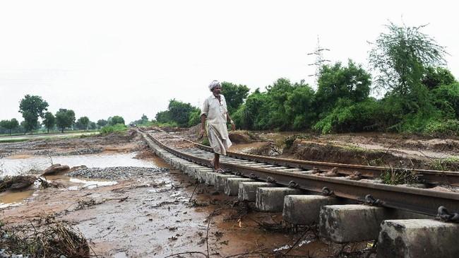 Banjir di Desa Godha, sekitar 196 kilometer dari Ahmedabad, Gujarat, menewaskan setidaknya 119 orang dan membuat 36 ribu harus dievakuasi. Banjir juga merusak infrastruktur seperti jalan dan rel kereta. (AFP PHOTO / SAM PANTHAKY)