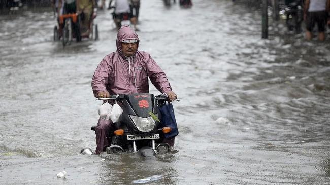 Sementara itu, curahan hujan yang tak kunjung reda membuat warga harus kreatif mencari jalan keluar dan transportasi alternatif. (AFP PHOTO / SHAMMI MEHRA)