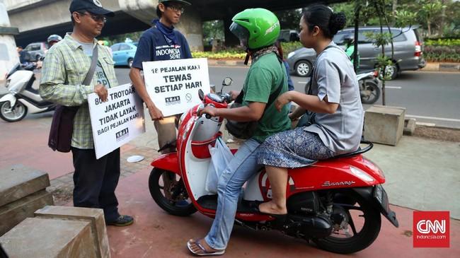 Pegiat Koalisi Pejalan Kaki menghalau pengendara motor yang melintasi trotoar di kawasan Casablanca, Jakarta. Minimnya kesadaran dan kedisiplinan pengendara motor di Jakarta membuat perlawanan pengendara motor kepada para pegiat ini ramai dibicarakan di media sosial. CNNIndonesia/Safir Makki