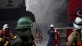 Namun, petugas kesulitan menjinakkan si jago merah lantaran jalan sempit dan lokasi pasar yang berhimpitan dengan bangunan lain. (AFP Photo/Behrouz Mehri)