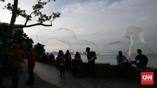 Tak jauh dari kawasan Padang Kota Lama, saat akhir pekan pengunjungberkumpul untuk menikmati pemandangan pantai. Aktivitas warga ditambah mainan gelembung air menjadi obyek foto jalanan. Menunggu momen yang pas adalah kuncinya.