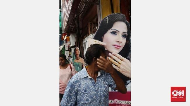 Poster iklan menjadi salah satu bagian elemen fotografi jalanan. Menunggu orang lewat dengan gestur tangan yang sama dengan gestur tangan poster perempuan membentuk kesan kesamaan dalam fotografi jalanan.