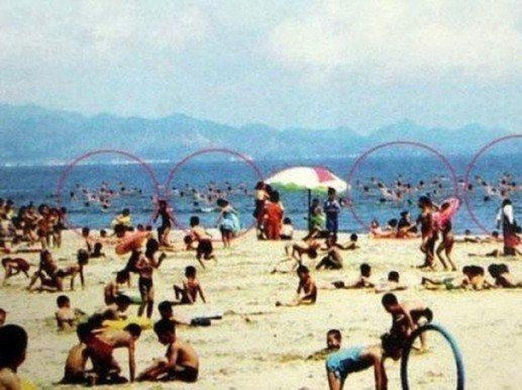 Pantai dengan latar belakang yang tampak ramai dan ceria. Tapi ternyata, gambar orang-orang berenang di laut itu identik satu dengan yang lain. Foto: Istimewa