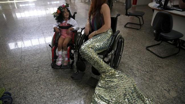 Pernah satu kali, di rumah sakit anak Disabled Child Care Association (AACD) di Sao Paulo,, ia berpakaian ala putri duyung duduk di atas kursi roda di samping anak kecil yang juga berkursi roda untuk memberi semangat. (Foto/REUTERS/Pilar Olivares)