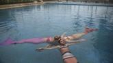 Catan melakukan latihan rutinnya di kolam renang di mana saja tersedia dan bisa digunakan. Sejumlah siswi berpraktik menjadi putri duyung. (Foto/REUTERS/Pilar Olivares)