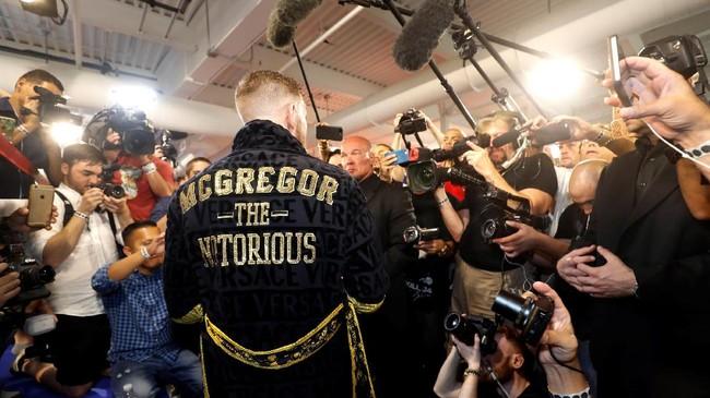 Conor McGregor mengenakan jubah hitam berbicara kepada awak media. McGregor mengaku tidak tertarik pindah ke ring tinju secara permanen meski bayarannya menggiurkan. (REUTERS/Steve Marcus)