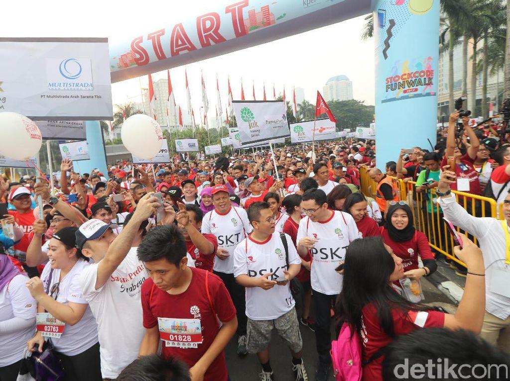 Para peserta mengikuti jalan santai Stockcode Funwalk di kawasan SCBD Sudirman, Jakarta, Minggu (13/8).
