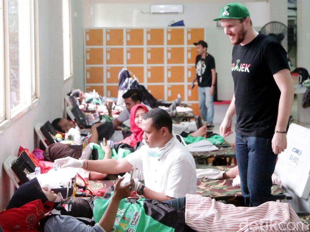 Chief Marketing Officer Go-Jek Indonesia, Piotr Jakubowksi mendampingi salah satu mitra driver Go-JeK yang tengah melakukan kegiatan donor darah yang digelar di Kantor operasional Go-Jek, Jakarta.