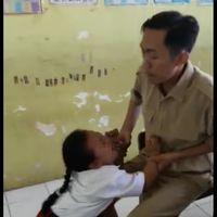 Karena terus meronta dan menangis sang guru pun duduk di bangku berusaha menenangkan muridnya. (Foto: Facebook/Atika Durrotin)