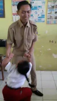 Sambil tersenyum sang guru perlahan berusaha membawa murid ke bagian tengah kelas. (Foto: Facebook/Atika Durrotin)