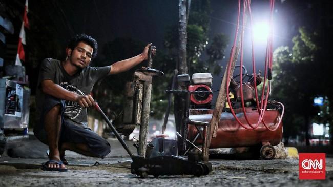 <p>Bisman Saleh Siregar (23), menjalani profesi tukang tambal ban sejak 2016, di depan Graha Induk KUD, Jalan Warung Buncit Raya, Jakarta. Ia melakoni pekerjaaannya dari jam 07.00 WIB sampai 23.00 WIB dengan pendapatan terbesar rata-rata Rp100 ribu per hari. (CNN Indonesia/Andry Novelino)</p>