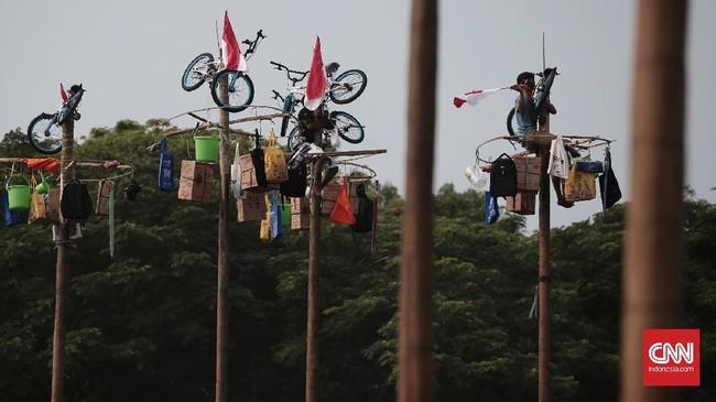 Warga berlomba-lomba di ajang panjat pinang kolosal di Pantai Carnaval Ancol, Jakarta, Kamis 17 Agustus 2017. Panitia menyiapkan 172 batang pohon pinang yang digantung hadiah dengan total Rp1,5 juta untuk merayakan HUT ke-72 RI. (CNN Indonesia/Andry Novelino)