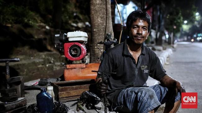 <p>Edy (43) menjalani profesi sebagai tukang tambal ban sejak tahun 2014, di Jalan Pejaten, Jakarta. Ia juga punya 'shift malam' yaitu 17.00 WIB hinga 01.00 WIB dengan pendapatan terbesar rata-rata Rp85 ribu per hari. (CNN Indonesia/Andry Novelino)</p>