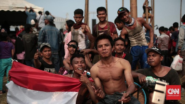 Warga membagi hasil hadiah dengan tim pemanjat pinang saat mengikuti lomba panjat pinang kolosal di Pantai Carnaval Ancol. (CNN Indonesia/Andry Novelino)