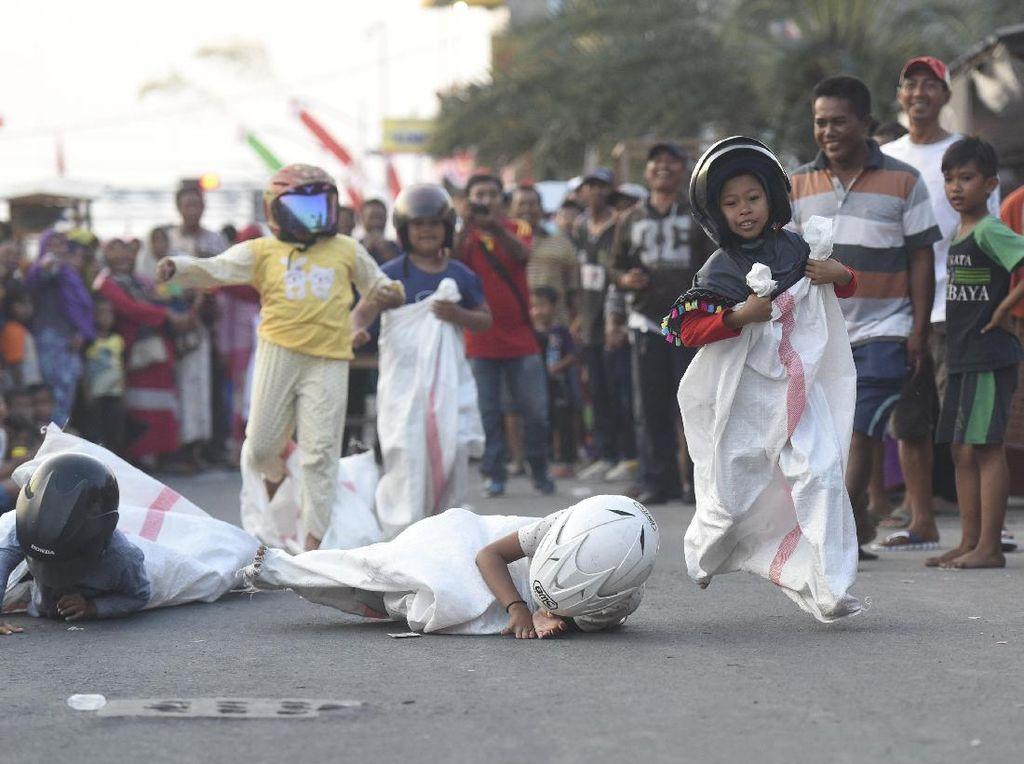 Sejumlah anak mengikuti lomba balap karung di Bulak, Surabaya, Jawa Timur, Jumat (11/8). Kegiatan tersebut diselenggarakan dalam rangka memeriahkan perayaan HUT ke-72 Kemerdekaan Indonesia. ANTARA FOTO/Zabur Karuru/kye/17