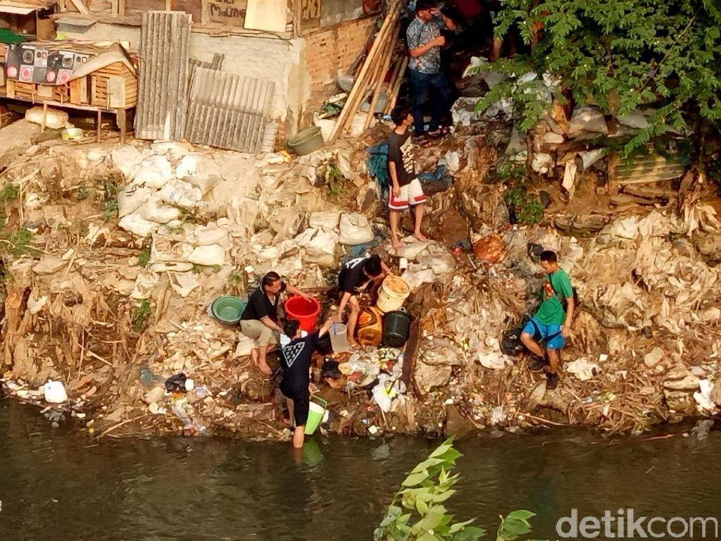 Petugas mengambil air dari sungai untuk membantu memadamkan api / Foto: Muhammad Fida Ul Haq/detikcom