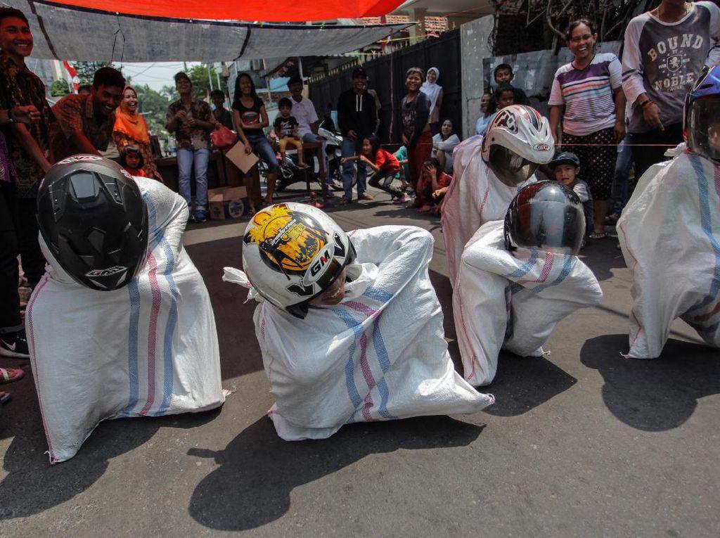 Sejumlah anak beradu cepat saat mengikuti lomba balap karung dengan mengenakan helm (Karung Race) di perumahan Persada Sayang, Kota Kediri, Jawa Timur, Minggu (20/8). Perlombaan unik itu menjadi favorit warga dalam memperingati HUT ke-72 RI. ANTARA FOTO/Prasetia Fauzani/pras/17